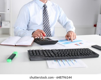Cheerful young businessman sitting at the table with laptop and stretching in the office