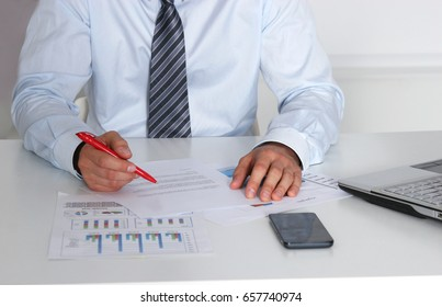 Cheerful young businessman sitting at the table in the office with laptop and looks at documents