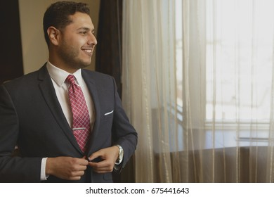 Cheerful young businessman smiling looking away thoughtfully buttoning his jacket dressing up for a business meeting standing at his hotel room copyspace positivity style fashion confidence preparing