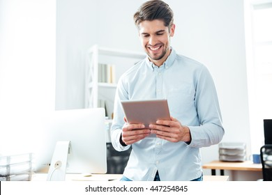 Cheerful young businessman standing and using tablet in office