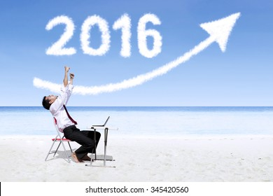 Cheerful young businessman working with laptop on the beach under clouds shaped numbers 2016 and upward arrow