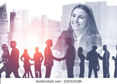 Cheerful young businesswoman shaking hands with her partner sitting with back to camera in white office. Double exposure of city. Business people silhouettes. Concept of hiring. Toned image