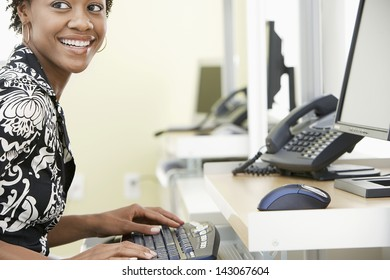 Cheerful young businesswoman typing on computer keyboard in office