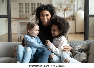 Cheerful young caring African ethnicity single mother embraces multi racial daughters sitting on couch in living room feels overjoyed look at camera. Adoption, childcare, happy family portrait concept