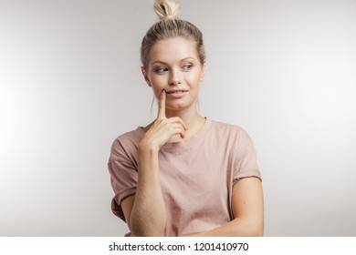 Cheerful young caucasian woman with blonde hair knot thinking about . Advertising or new idea concept