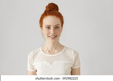 Cheerful young Caucasian woman with freckles and ginger hair in bun looking and smiling happily at camera, wearing white blouse. Redhead girl with pretty joyful smile posing at blank studio wall