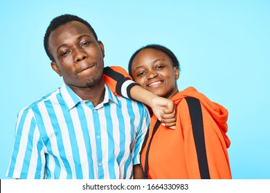 Cheerful young couple of African appearance amusement hugs communication