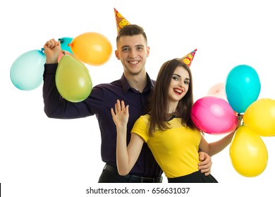 Cheerful young couple with balloons in their hands smiling