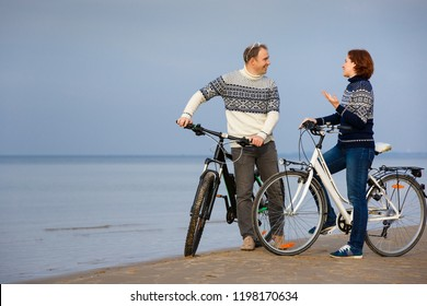 Cheerful young couple biking on beach on a sunny day