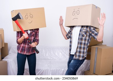 Cheerful young couple with cardboard boxes on their heads. A woman holds an ax.