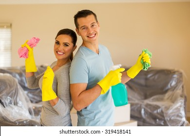 cheerful young couple cleaning their new house