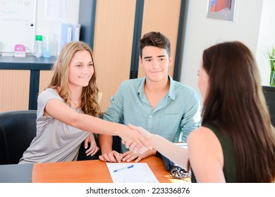 cheerful young couple handshaking after a successful transaction with business woman in office