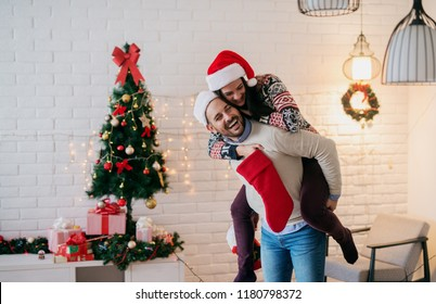 Cheerful young couple having fun while decorating their apartment for coming christmas. Boy caring his girlfriend on his back.