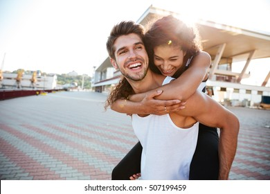 Cheerful young couple having fun and laughing together outdoors
