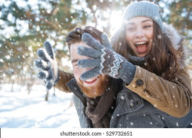 Cheerful young couple having fun in winter park