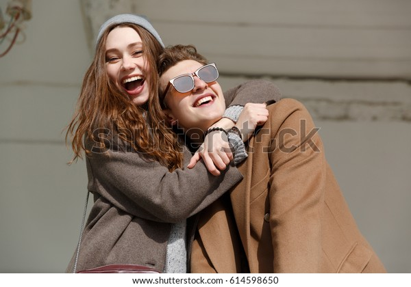 Cheerful young couple hugging and having fun outdoors in autumn