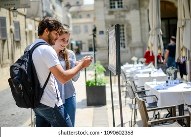cheerful young couple looking at restaurant menu on a cultural weekend city trip discovering together historical european city in summer