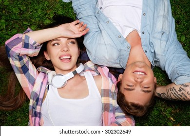 Cheerful young couple lying on a grass in a park