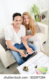 cheerful young couple making project to makeover and renovate their new house