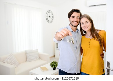 cheerful young couple man and woman holding keys and welcome friends at open front door new student home apartment