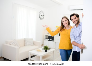 cheerful young couple man and woman welcome friends at open front door new student home apartment