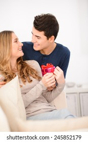 cheerful young couple man and woman at home offering gifts for lovers day