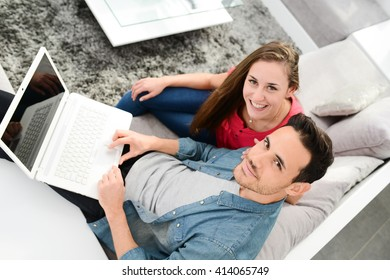 cheerful young couple man and woman in sofa at home with laptop computer