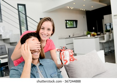 cheerful young couple offering a gift present for birthday or valentines day