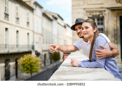 cheerful young couple on a cultural weekend city trip discovering together historical european city in summer