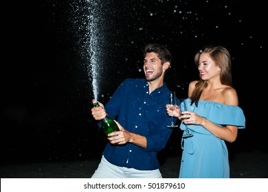 Cheerful young couple opening bottle of champagne and having fun at night