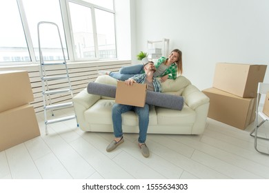 Cheerful young couple rejoices in moving to a new home laying out their belongings in the living room. Concept of housewarming and mortgages for a young family
