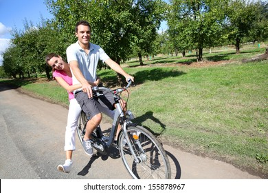 Cheerful young couple riding bikes in countryside