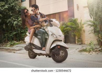 Cheerful young couple riding on a motorbike