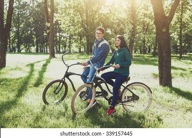 Cheerful young couple riding a retro bike and smiles. Young lovers couple ride a bike outdoors