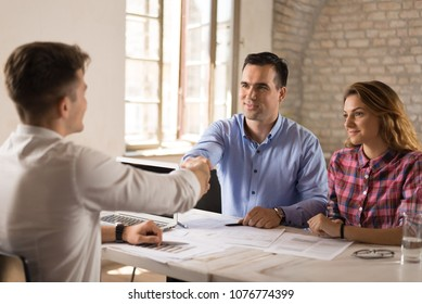 Cheerful young couple shaking hands with the insurance agent.