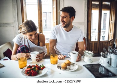Cheerful young couple sitting by table at breakfast and laughing.