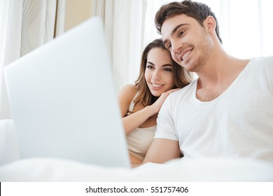 Cheerful young couple smiling and using laptop in bed
