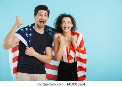 Cheerful young couple standing isolated over blue background, wearing american flag