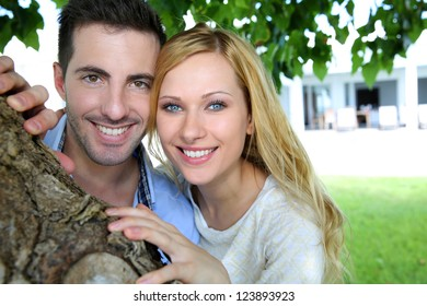Cheerful young couple standing under tree