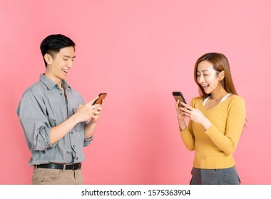 Cheerful young couple standing and watching the smart phone