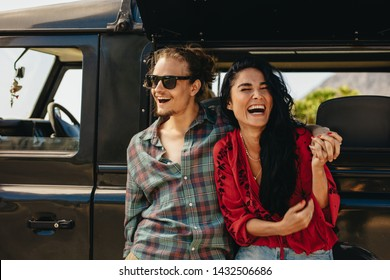 Cheerful young couple taking a break on roadtrip. Young man and woman standing by their car and laughing.
