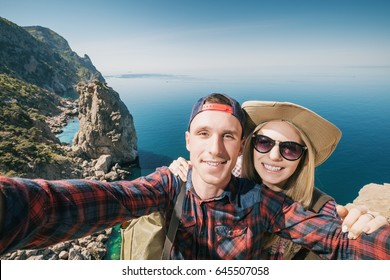 Cheerful young couple taking selfie outside. Happy man and woman photograph self on the background of beautiful nature in the mountains near the sea.