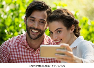 Cheerful young couple taking slefie through smart phone at park