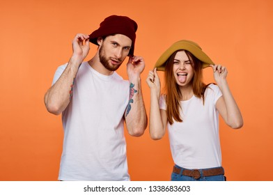 Cheerful young couple in white T-shirts and hats orange background