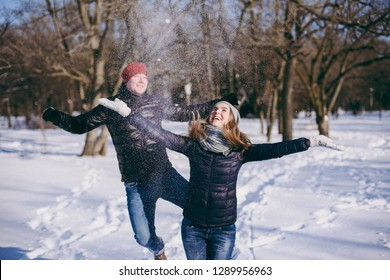 Cheerful young couple woman and man in winter warm clothes jumping, throwing snow walking in snowy park or forest outdoors. Winter fun, leisure on holidays. Love relationship people lifestyle concept