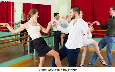 Cheerful young couples dancing active dance at studio