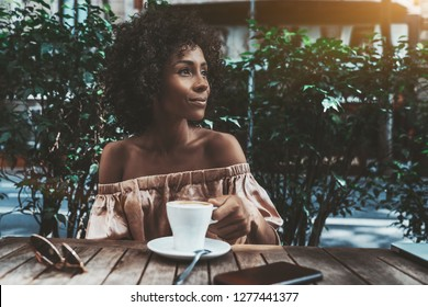 A cheerful young curly female is drinking coffee in a street bar and looking aside; a dazzling happy biracial woman with a cup of tasty hot chocolate is relaxing in a street cafe