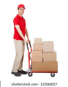 Cheerful young deliveryman in a red uniform holding trolley loaded with cardboard boxes isolated on white