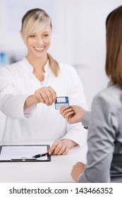 Cheerful young doctor giving insurance card to a patient