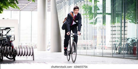 Cheerful young employee with a healthy lifestyle riding an utility bicycle to a modern workplace in Berlin